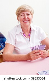 happy senior woman playing card