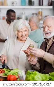 happy senior woman pointing with finger at bottle with oil near retired man and multicultural friends on blurred background