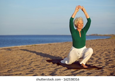 Happy senior woman practicing yoga on the sandy beach. Mature caucasian woman stretching legs and arms on the seashore. Healthy lifestyle and fitness concept