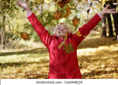 Happy senior woman in red coat throwing up yellow leaves in the autumn park, happy retirement concept, healthy lifestyle, outdoor portrait