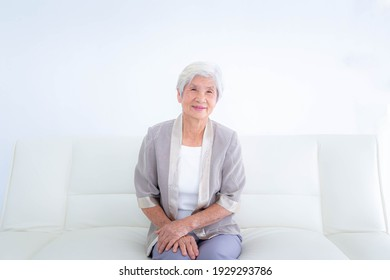 Happy senior woman relaxing on couch at home in the living room.