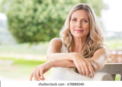 Happy senior woman relaxing on bench in the lawn. Close up face of a mature blonde woman smiling and looking at camera. Retired woman in casuals sitting outdoor in a summer day.
