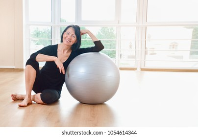 Happy senior woman resting after exercise. Fit aged woman lean on the big gray exercise ball.