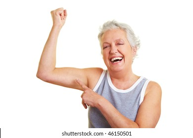 Happy senior woman showing her upper arm muscles