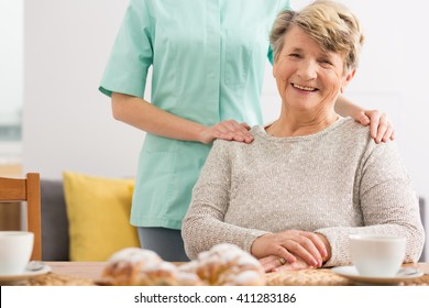 Happy senior woman sitting beside table and her carer