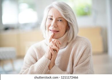 Happy senior woman sitting at home
