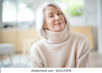 Happy senior woman sitting at home