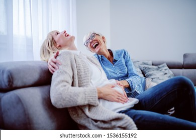 Happy senior woman sitting next to her pregnant daughter on sofa in living room and touching her belly. Both women are laughing.
