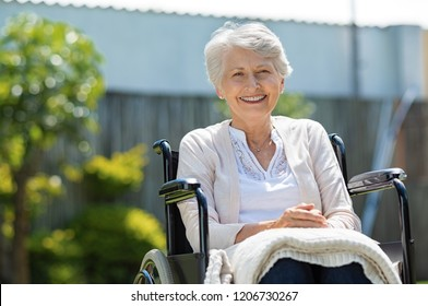 Happy senior woman sitting on wheelchair and recovering from illness. Handicapped mature woman sitting in wheelchair looking at camera. Portrait of a disabled elderly woman outdoor in a nursing home.