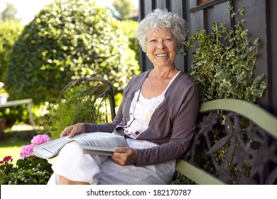 Happy senior woman sitting on bench in her backyard garden with a newspaper looking at camera smiling