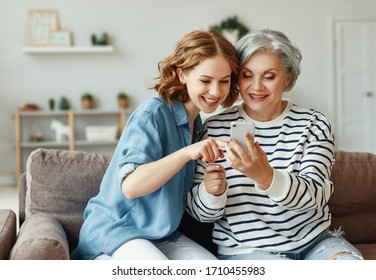 Happy senior woman smiling and sharing data on smartphone with young daughter while sitting on couch at home together