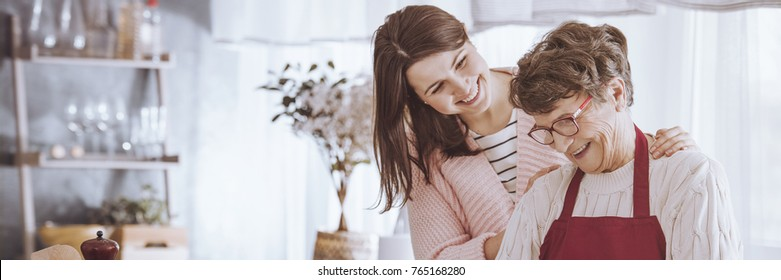 Happy senior woman smiling while spending precious moments with her young granddaughter cooking and chatting together