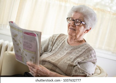 Happy senior woman solving a crossword puzzle at home.