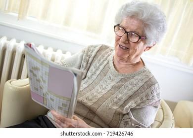 Happy senior woman solving crossword puzzle at home.