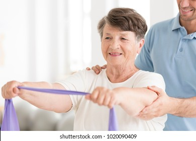 Happy senior woman stretching with elastic tape during rehabilitation