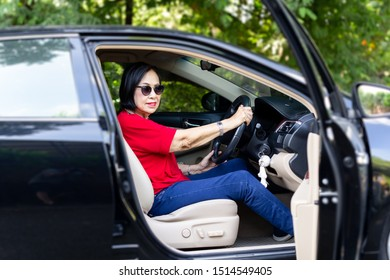 Happy senior woman in sunglasses driving a car.