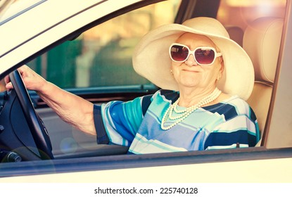 happy senior woman in sunglasses and hat driving automobile .