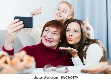 Happy senior woman taking selfie with her adult daughter and granddaughter at home