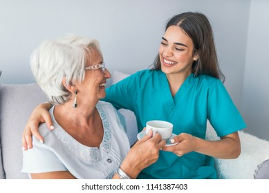 Happy senior woman talking with friendly nurse at geriatric ward. Helpful young pretty woman and lovely older lady. Professional helpful caregiver comforting smiling senior woman at nursing home