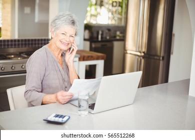 Happy senior woman talking on mobile phone at kitchen