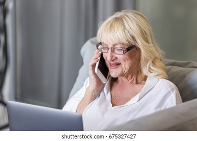 Happy senior woman talking on mobile phone while using laptop at home on a couch