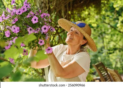 Happy senior woman tends the flowers in a hanging pot. There is a green background of blurred plants, and wooden outdoor chairs are visible in the lower right corner.