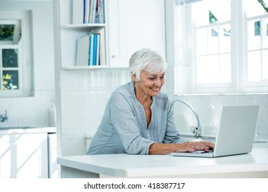 Happy senior woman using laptop while standing at home