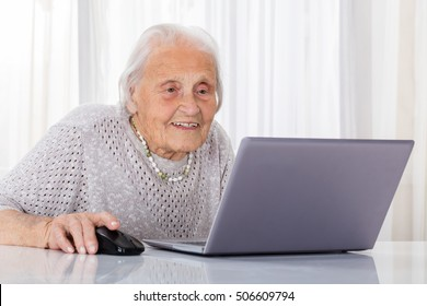 Happy Senior Woman Using Laptop On Desk At Home