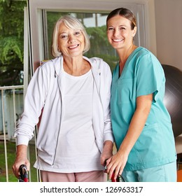 Happy senior woman with walker and nurse in a physiotherapy