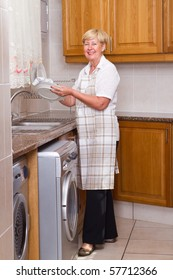 happy senior woman washing dishes in kitchen