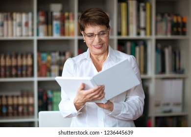 Happy senior woman wearing glasses head shot in a white shirt,  with book against the background of a bookcase