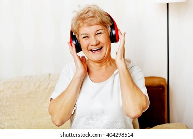 Happy senior woman wearing red headphones