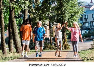 happy senior women giving high five in park near multicultural retired men