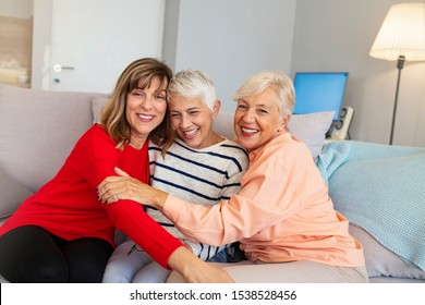 Happy senior women smiling and hugging at home. Three seniors hugging. Senior women laughing together indoors. Group of elderly friends posing together. Portrait of beautiful senior friends