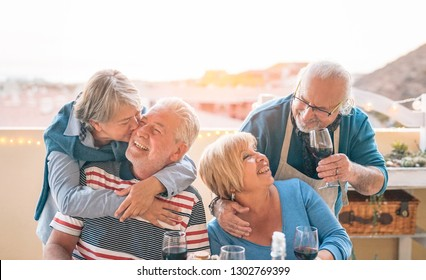 Happy seniors couple having fun dining together on terrace - Romantic older people drinking wine and enjoying a sunny day  on rooftop - Friendship, retirement and elderly lifestyle activities concept