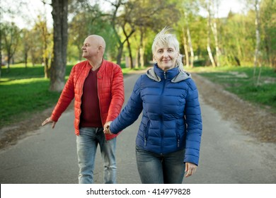 happy seniors couple hold hands and walk; older male and female in park;