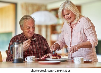 Happy seniors couple while eating cake together in the living room