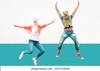Happy seniors crazy couple wearing unicorn and t-rex mask while jumping outdoor - Mature trendy people having fun celebrating outside - Absurd concept of masquerade funny holidays