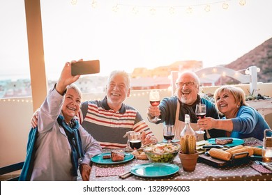 Happy seniors friends taking selfie with mobile smartphone camera at barbecue dinner - Mature people having fun eating and drinking red wine on patio while using new trends technology phone apps