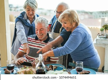 Happy seniors friends using smartphone at barbecue dinner in house terrace - Mature people having fun with new trend technology - Focus on left man face