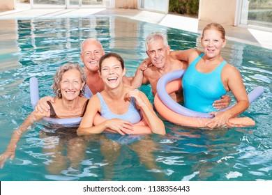 Happy seniors group is doing aquafitness course in rehab pool