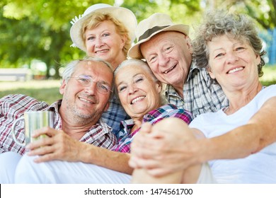 Happy seniors group as friends on a tour in summer in nature