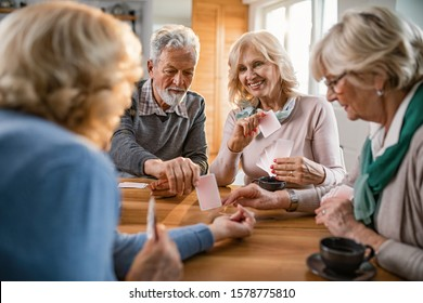 Happy seniors having fun while playing card game at home.
