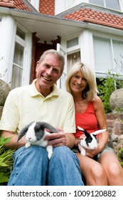 Happy seniors hold rabbits