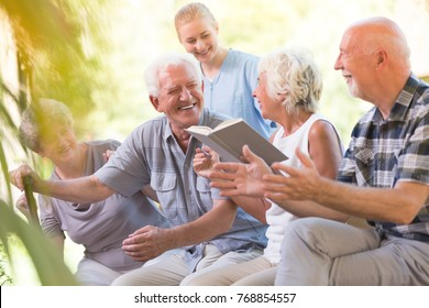 Happy seniors from nursing house spending day outside and reading book together