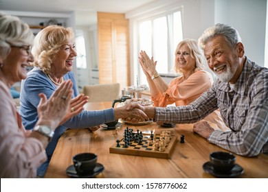 Happy seniors shaking hands and congratulating each other after playing chess game at home. Focus is on woman in blue sweater.