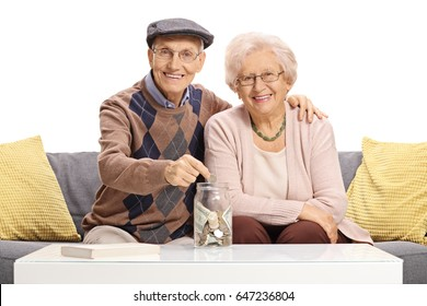 Happy seniors sitting on a sofa and putting a coin into a money jar isolated on white background
