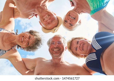 Happy seniors in summer vacation hugging each other as friends in circle
