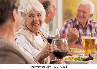 Happy seniors talking and smiling during dinner, drinking beer and wine