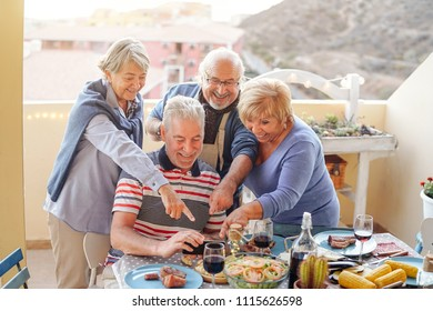 Happy seniors watching on mobile smart phone at dinner on terrace - Retired people having fun dining together and using new smartphone technologies - Elderly activities and tech addiction concept